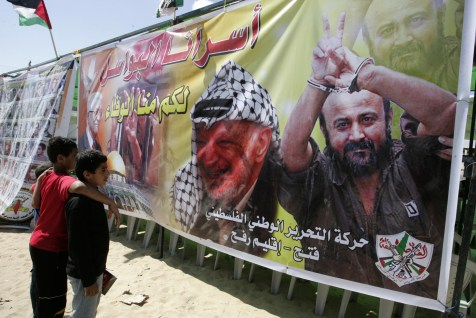 Palestinian children look at a poster of Yasser Arafat and Marwan Barghouti