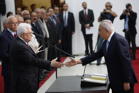 PA President Mahmoud Abbas (L) and his Prime Minister Salam Fayyad (R), shake hands during the swearing in ceremony of the new cabinet, at Abbas's headquarters in the West Bank town of Ramallah, on 16 May 2012.
