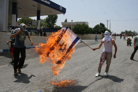 Palestinian protesters burn an Israeli flag