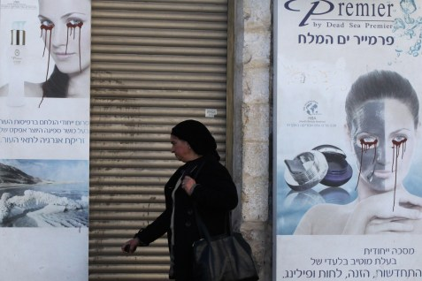 Religious woman walking by a vandalized poster in Jerusalem