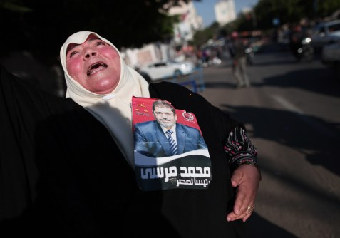 A Palestinian woman holds a picture of Egypt's new president, the Muslim Brotherhood's Mohamed Morsi