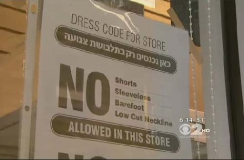 Williamsburg storefront sign bans immodest attire.