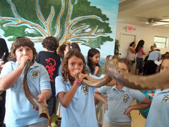 Children blowing shofar at Chabad Hebrew After-School.