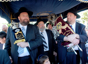 (L-R) Yisroel Zev Rechnitz, Rav Yaakov Rechnitz and Shlomo Yehuda Rechnitz leading the Torah procession through the streets of Los Angeles. 