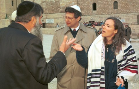 An orthodox Jewish man argues with a reform Jewish woman wearing a prayer shawl at the Kotel.