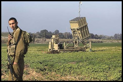 "An Israeli soldier standing next to a launcher, part of the ""Iron Dome"" missile defense system."