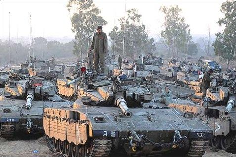 Israeli soldiers sit atop a tank at a staging area outside the central Gaza Strip November 22, 2012.