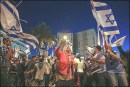"Israelis wave flags and signs saying ""Together We'll Win"" during a demonstration supporting an Israeli ground operation in Gaza."