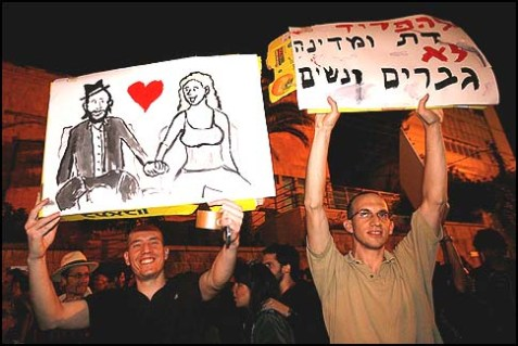 """Hundreds of secular Israelis demonstrating against segregation between men and women on buses. The sign read: """"Separate religion from the state, not men from women."""""""