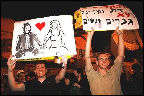 "Hundreds of secular Israelis demonstrating against segregation between men and women on buses. The sign read: ""Separate religion from the state, not men from women."""