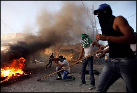 Masked Palestinians throwing stones at Israeli security forces, in the Shuafat refugee camp on the outskirts of Jerusalem, September 18, 2012.