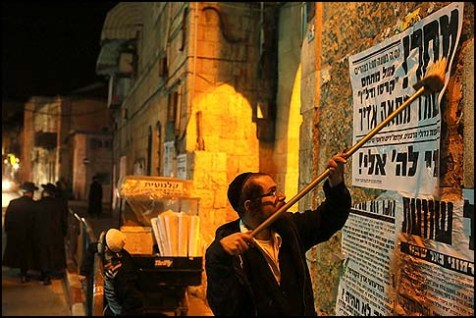 "A Haredi man posting ""pashekvilim"" in Meah Shearim, in Jerusalem."