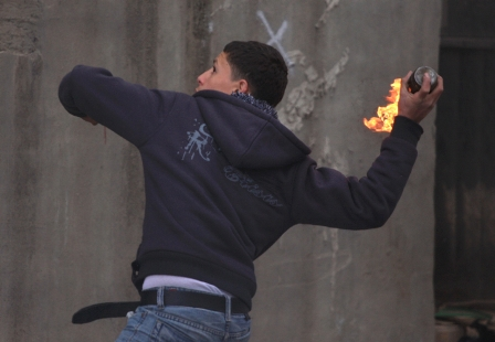 A Palestinian Authority Arab prepares to hurl firebomb at Israeli soldiers. (archive)