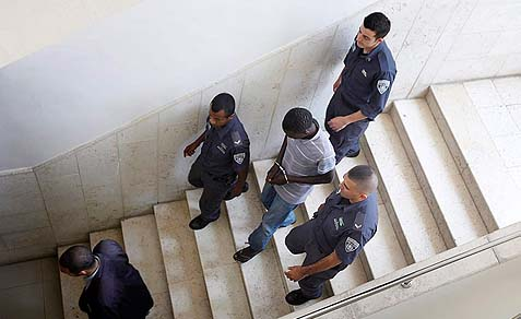 24 year old Sudanese refugee Mohammed Fadoul, one of the four suspects arrested for raping a young girl at a high school dance, being escorted by police in the Jerusalem District Court, May 10, 2012.