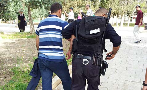 Israeli policeman taking a stone throwing suspect into custody.