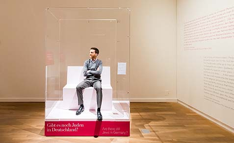 The Jewish Museum Berlin's Leeor Englishman is sitting in his showcase, ready to answer visitors' questions.