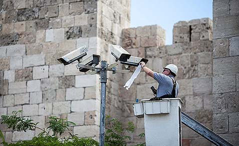 A technician fixing security cameras located near the old city of Jerusalem.