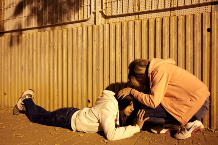 Israeli women take cover as a siren sounds warning about incoming rocket fired from Gaza