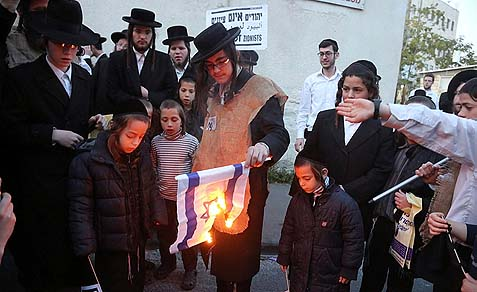 Neturei Karta kids burning an Israeli flag on Israel's 65th birthday.