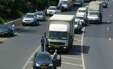 Israelis stand still on the Ayalon Highway as a siren is sounded across the country to mark Memorial Day.