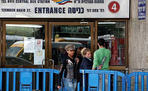 Security guard checking a man for weapons and explosives before letting him enter the Central Bus Station in Tel-Aviv.