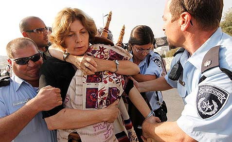 The WOW's Anat Hoffman holding a torah scroll in confrontation with police on July 12, 2010.