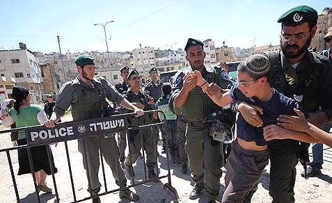 Police forcefully evict a boy from Jewish-owned Beit Machpella in Hebron, April 4, 2012.