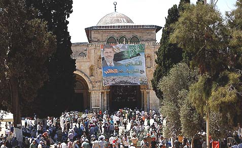 Palestinian supporters of Egypt's ousted President Mohammed Morsi walk by his portrait hung on a wall at the Al-Aqsa Mosque in Jerusalem's Old City, Friday, July 12, 2013.
