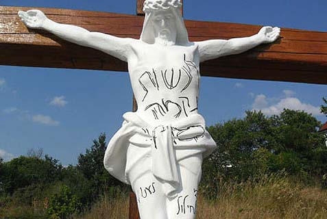 A figure of Jesus on the cross defaced in Hebrew opposite the grave of Rabbi Nachman in Uman, Ukraine, Aug. 14, 2013.