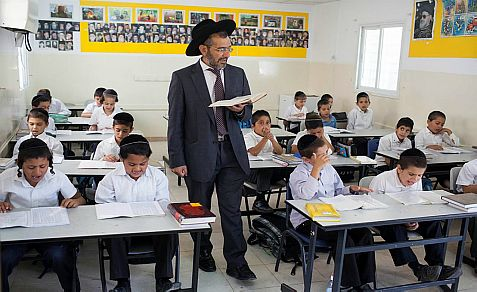 Young Ultra Orthodox kids sit in a classroom in a school in the neighborhood of Neve Yaakov in Jerusalem