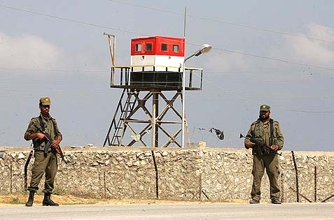 Palestinian Hamas security stand guard near an Egyptian watch tower on the border with Egypt in Rafah, southern Gaza Strip.