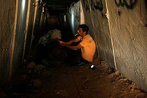 A Palestinian tunnel worker lights a cigarette for his colleague inside a smuggling tunnel dug beneath the Gaza-Egypt border in the southern Gaza Strip on August 27, 2013. Egyptian security forces have stepped up a crackdown campaign on smuggling tunnels as part of the establishment of a no man's land along the border.