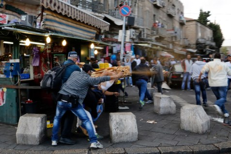An undercover Israeli policeman use pepper spray during an Arab riot, in front of Jerusalem's Old  City's Damascus gate on September 24, 2013.