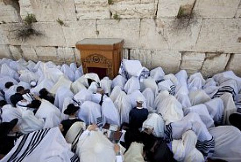Worshippers cover themselves with prayer shawls at he Western Wall in Jerusalem during the Kohenim Benediction priestly blessing