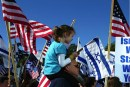 Man holds daughter on shoulders at Pro-Israel Rally
