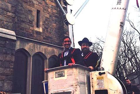 Senator Jeffrey D Klein (D), the anti-boycott bill's sponsor, riding a cherry picker with a Chabadnik on Chanukah.