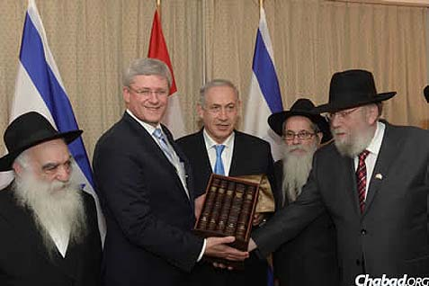 From left: Rabbi Berel Mockin, Prime Minister Stephen Harper, Prime Minister Benjamin Netanyahu, Rabbi Zalman A. Grossbaum and Rabbi Rabbi Yitzchok Wineberg, as Rabbi Wineberg presents Harper with a Chumash that includes commentaries of the Rebbe.