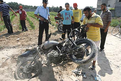 Palestinians inspect at a motorcycle that was hit in an Israeli air strike in Dir al-Balah in the central Gaza Strip in 2012, similar to Sunday's attack.