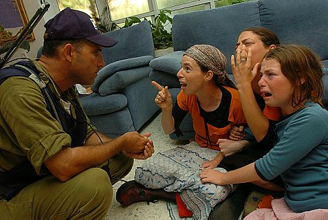 An Israeli soldier evacuates Jews from their home in  Nevei Dekalim in 2005..
