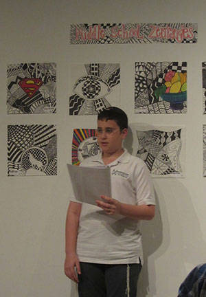Hebrew Academy Middle School student Jack Benveniste-Plitt reads his poem to the audience.