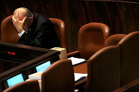 Ehud Olmert, in a picture from 2008, is rightfully hiding his face.