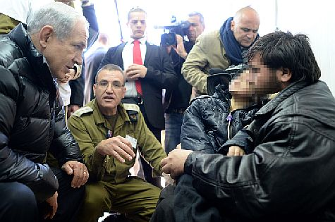 Prime Minister Binyamin Netanyahu speaks with wounded Syrian at an IDF field hospital in the Golan Heights