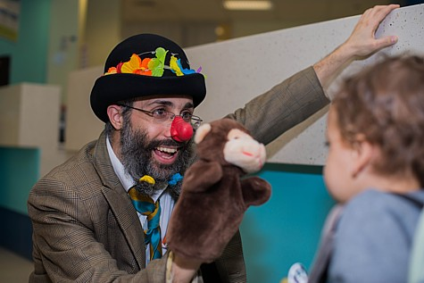 Reuven the Clown carries out play therapy with a young child. (illustrative)