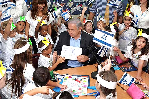 Prime Minister Benjamin Netanyahu surrounded by Israeli school children. The man who could be king.