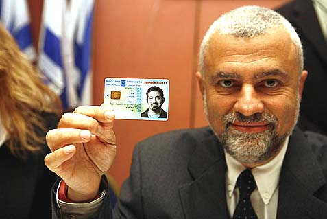 "An employee of the Ministry of the Interior showing a sample Israeli ""smart"" ID card. Now it turns out the people in charge of Israel's security would rather not be associated with this project."