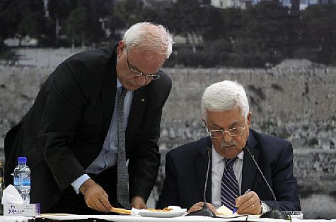 Palestinian Authority Chairman Mahmoud Abbas (R) and chief negotiator Saeb Erekat, sign a membership application to 15 U.N. agencies in Ramallah, Tuesday, April 1, 2014.  in a move that could derail a US push to revive faltering framework talks with Israel.