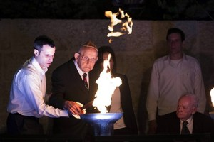 Holocaust survivor Zvi Michaeli lights a torch with his grandson during a ceremony at the Yad Vashem Holocaust Memorial Museum in Jerusalem, as Israel marks the annual Holocaust Remembrance Day on April 27, 2014.