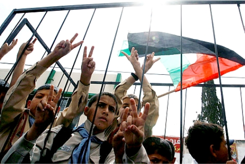 Palestinian boys stand behind mock jail bars during a rally calling for the release of Palestinian prisoners from Israeli jails (but not from Palestinian Arab jails), in Rafah in the southern Gaza Strip on April 20, 2014.