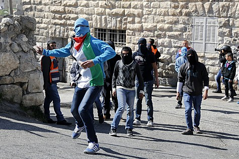 Palestinian youth hurl stones at Israel Police forces (unseen) during clashes with Police after friday prayers in the east Jerusalem neighborhood of Ras Al Amoud on February 28, 2014, Jerusalem, Israel. Police today in order to prevent riots limted the entrance for Muslim worship to men over age 50. Photo by Sliman Khader/Flash90