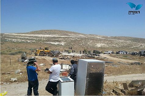 Arab workers wait to pack belongings of now-homeless Jews at Ma'aleh Rehavam after demolitions in Gush Etzion on May 14, 2014.